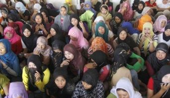 Indonesian workers ready to fly to Saudi Arabia to work as maids wait at a shelter during a police inspection in Bekasi