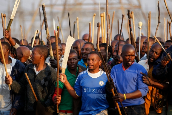 Striking miners chant slogans outside a South African mine in Rustenburg