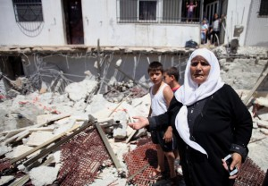 Palestinians look at the rubble of a store following demolished their sheds by Israeli bulldozers, in Ras al-Amud in Jerusalem