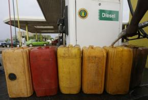 A man fills containers with diesel at a petrol station in Abuja, Nigeria, Tuesday, May 26, 2015. Nigeria's outgoing government has agreed to pay a debt of $800 million to resolve a months-long fuel crisis crippling the economy days before the inauguration of a new president in the country, oil suppliers said Wednesday. (AP Photo/Sunday Alamba)